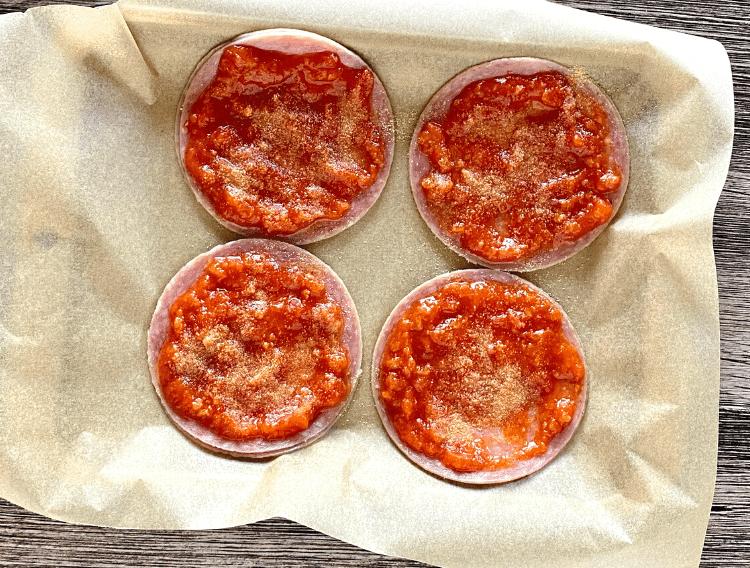 sauce and garlic powder layered on salami on lined baking sheet