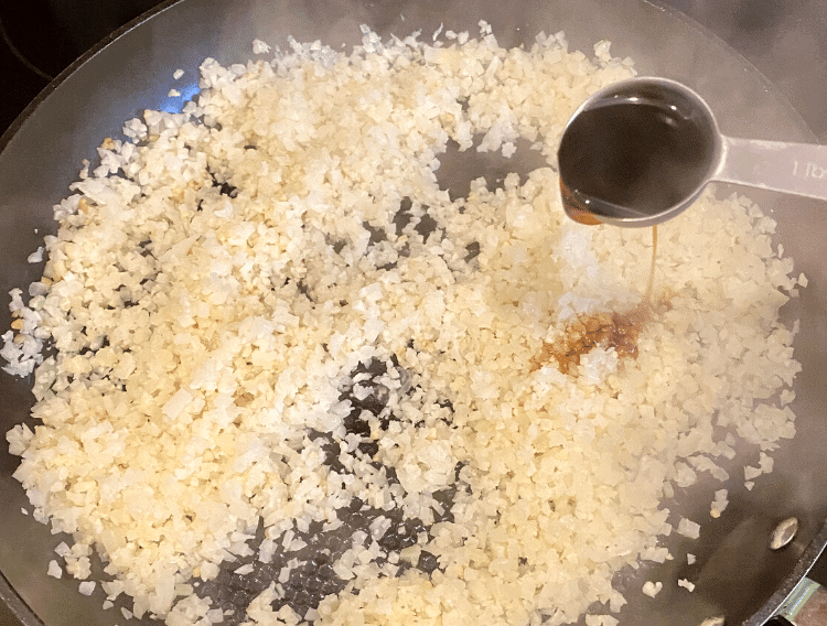 pouring coconut aminos on coconut cauliflower fried rice