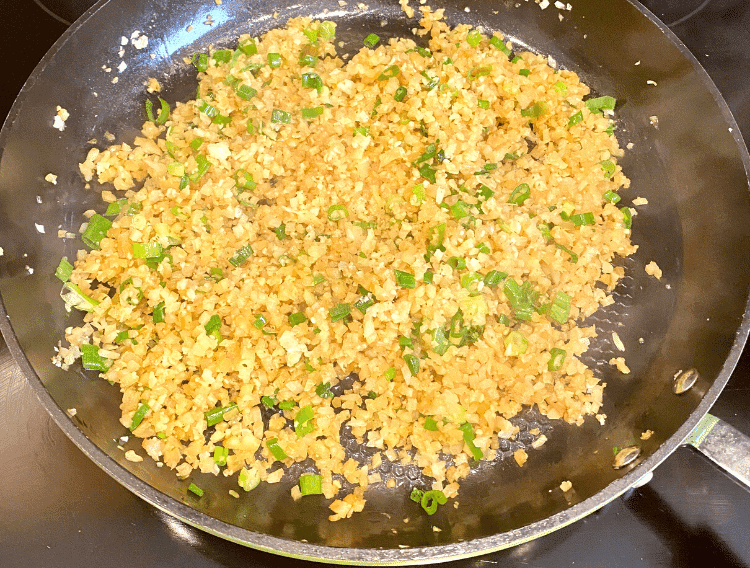 keto fried cauliflower rice with green onions in a skillet
