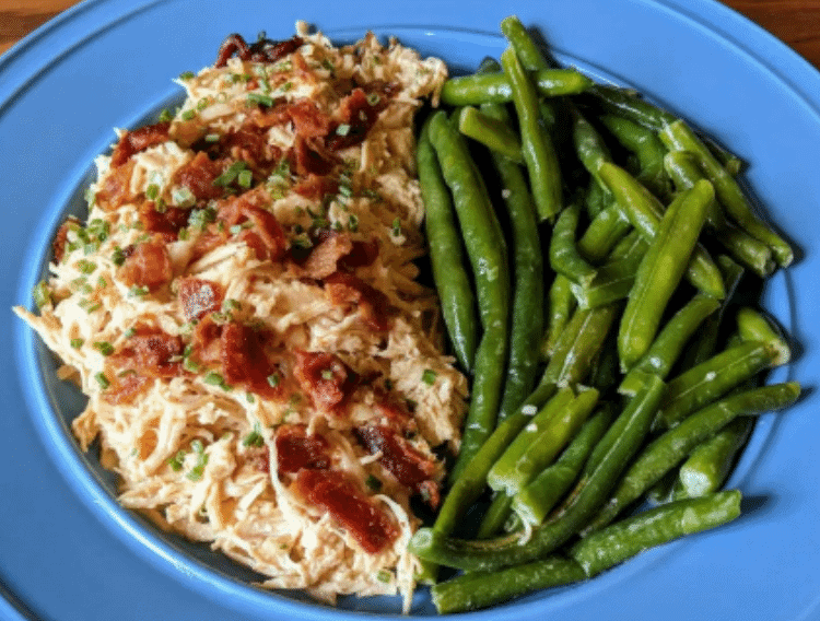 shredded chicken and bacon on a blue plate with green beans