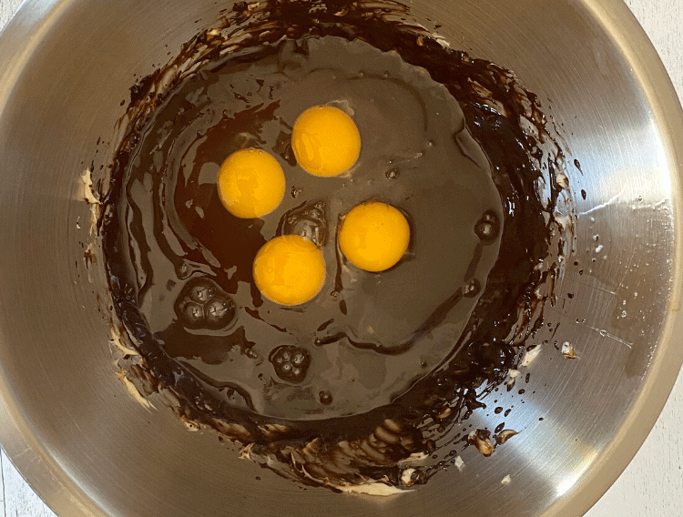 eggs in chocolate butter mixture for keto chocolate cupcakes