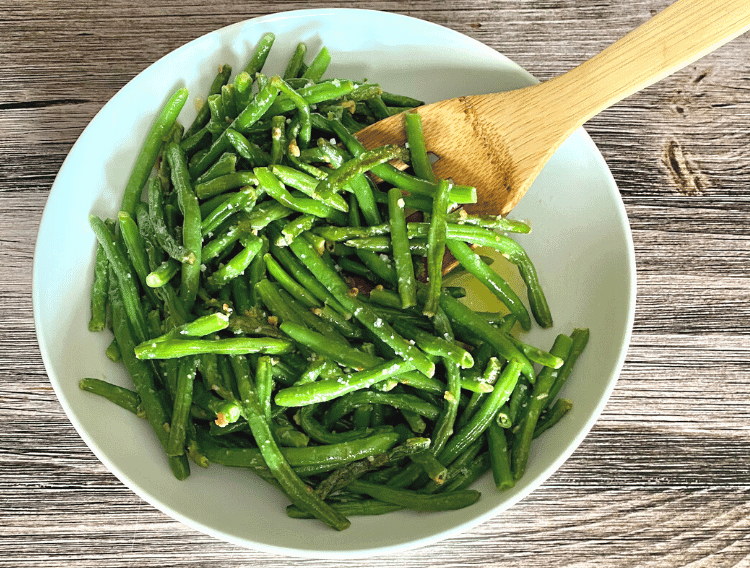 low carb garlic green beans with a wooden spoon