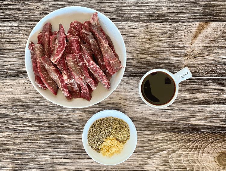 keto garlic steak strip ingredients on a wooden board