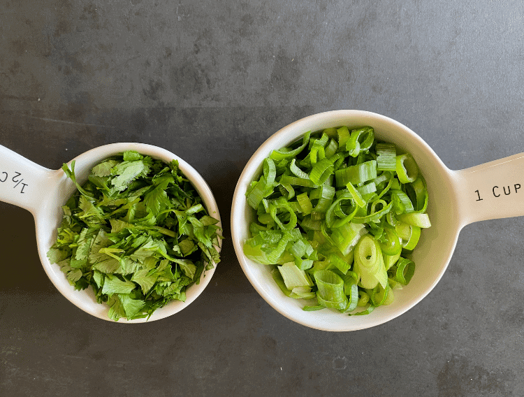 Cilantro and green onions in measuring cups on a black background