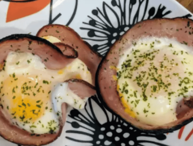 keto ham and egg cups on a white plate with red flowers
