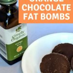 orange chocolate fat bombs on a white plate and a bottle of Simply Organic orange flavoring