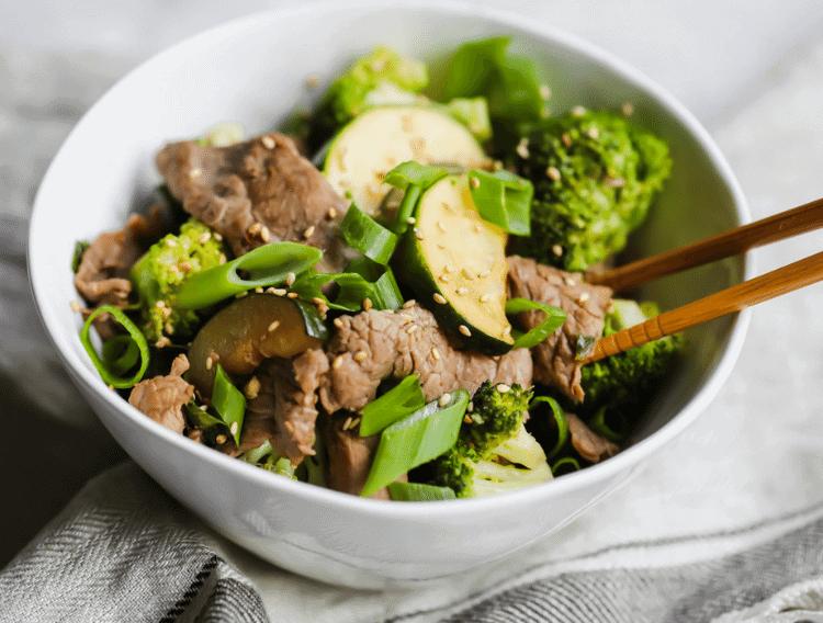 keto garlic steak stir fry in a white bowl with chopsticks