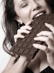 woman eating chocolate bar, female eating her sweet cravings, girl biting chocolate bar