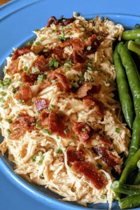 Shredded chicken topped with bacon and green beans on a blue plate