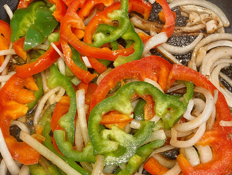 peppers and onions sauteeing in a pan