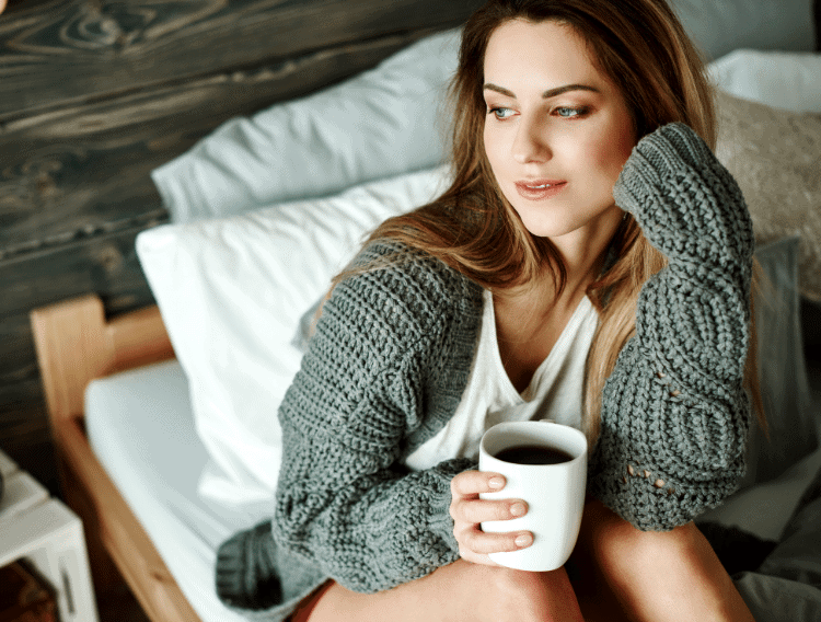 woman drinking coffee while intermittent fasting on a bed