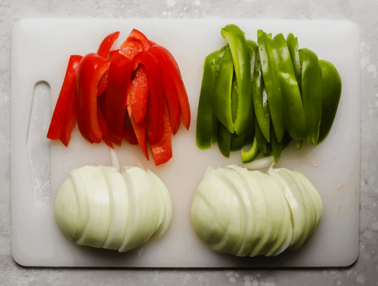 red peppers, green peppers and onions on a cutting board