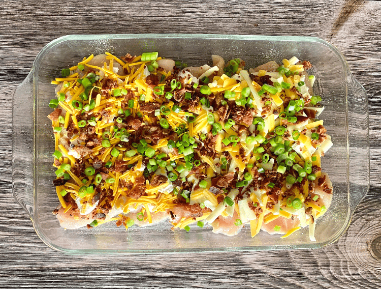 cheesy bacon chicken topped with green onions in casserole dish