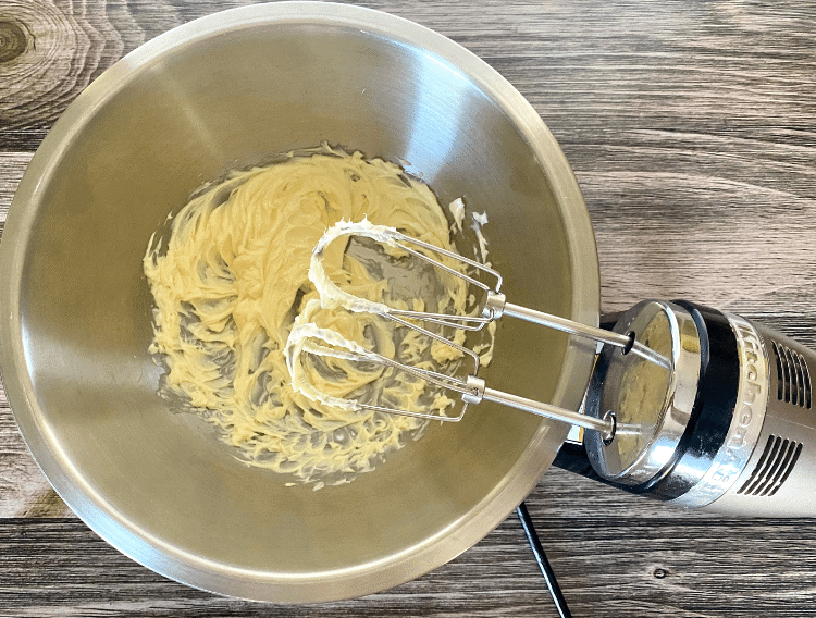 whipped butter in a mixing bowl with hand mixer
